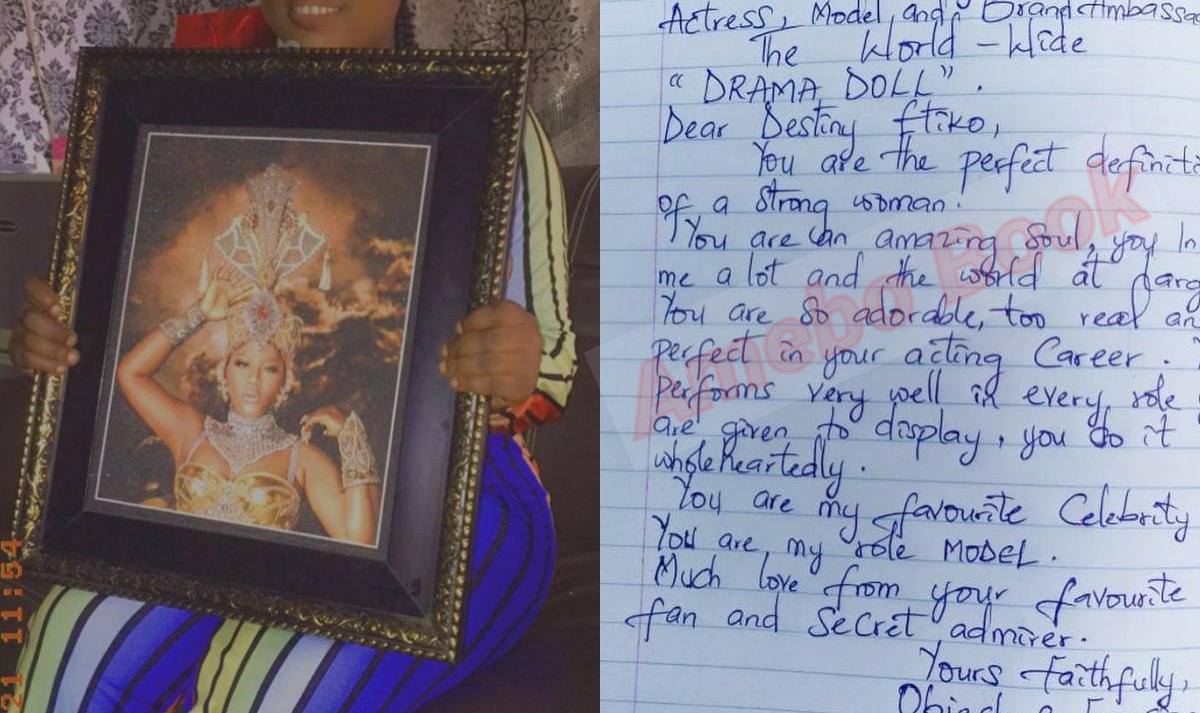 Lady With Framed Photo Of Destiny Etiko Writes Letter